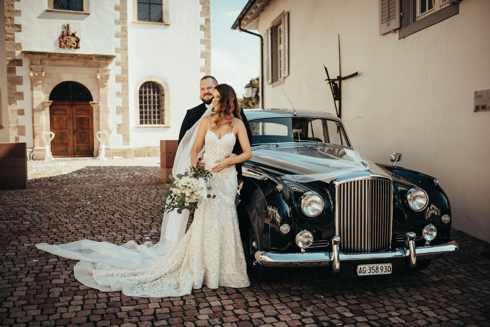 Couple after the ceremony with their Bentley S2 from Emil Frey Classics